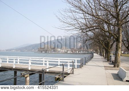 The Embankment Of The Lake With Trees, A Wooden Bridge And Trees Along The Embankment.