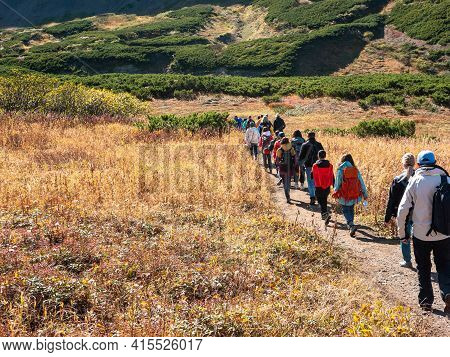Tourists Walk Along The Vachkazhets Ridge. Group Of People Went On A Hike To Explore The Nature Of K