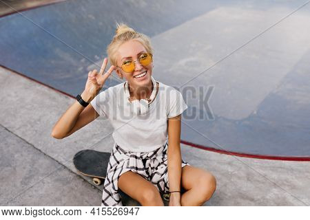 Pretty Skater Girl With Trendy Hairstyle Posing With Peace Sign. Fashionable Tanned Lady In Headphon