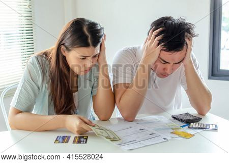 Stressed Young Couple Holding Credit Card And Worried About Family Budget Expense Cost Bills And Cal