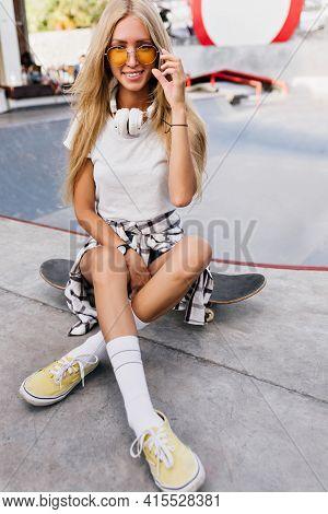 Enchanting Woman In White Socks Sitting On Skateboard. Charming Skater Girl With Long Blonde Hair Sm