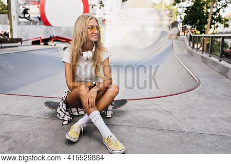 Gorgeous Tanned Skater Girl Posing Outdoor. Photo Of Smiling Female Model In Sport Shoes Sitting Wit