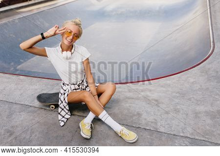 Funny Skater Girl With Trendy Hairstyle Expressing Positive Emotions. Outdoor Portrait Of Joyful Fem