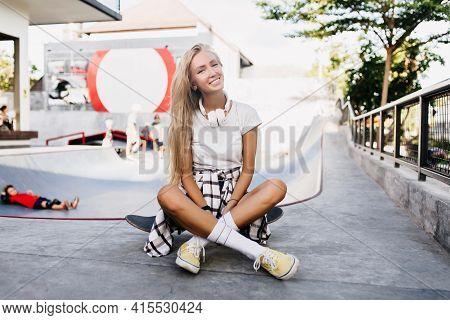 Glad Slim Girl Sitting On Longboard After Training. Outdoor Portrait Of Pretty Blonde Female Model P
