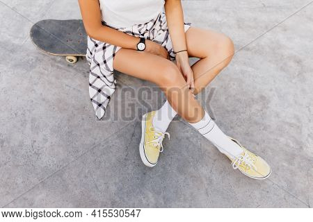 Overhead Photo Of Tanned Caucasian Girl Chilling In Skate Park After Training. Magnificent Woman Wea