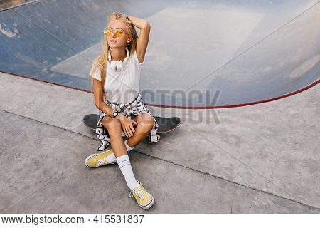 Pretty Woman With Tanned Skin Sitting On Skateboard And Playing With Blonde Hair. Outdoor Photo Of W