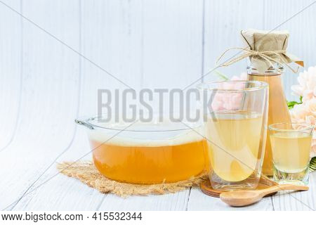 Scoby And Kombucha Tea In Bowl Glass On Wood Background, Cider Fermented Drink. Benefits Of Kombucha