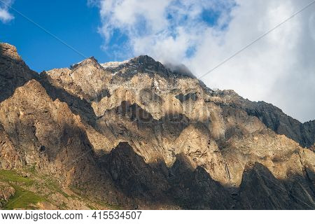 Scenic Mountain Landscape With Great Rocks In Golden Sunlight And Low Clouds. Awesome Rocky Wall Wit