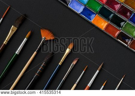 Different Shape And Size Paintbrushes, Set Of Watercolor Paints On Black Paper Sheet, Top View, Flat