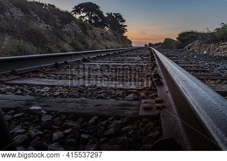 Parallel Train Tracks Lead Up To The Horizon As Dawn Begins To Light The Morning Sky.