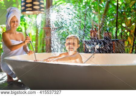 Happy Baby Boy With Mother Have Fun In Bath. Playful Woman Spraying Child From Shower In Outside Bat