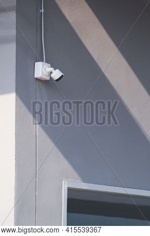 Perspective Side View Of Security Camera And Flexible Metal Conduit With Part Of Glass Window On Gra