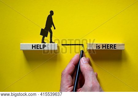 Help Is Here Symbol. Wooden Blocks With Words 'help Is Here' On Beautiful Yellow Background. Busines