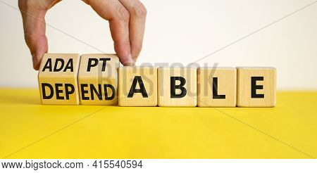 Adaptable Or Dependable Symbol. Businessman Turns Wooden Cubes And Changes The Word Dependable To Ad