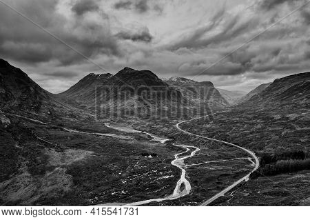Flying Drone Dramatic  Black And White Landscape Image Of Mountains Rivers And Valleys In Glencoe In