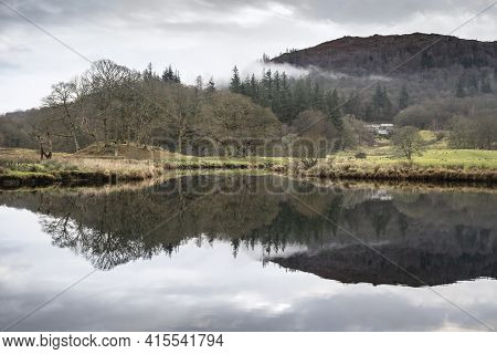 Epic Dramatic Landscape Image Looking Across River Brathay In Lake District Towards Langdale Piks Mo