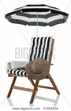 Beach chair with umbrella, sunhat and towel