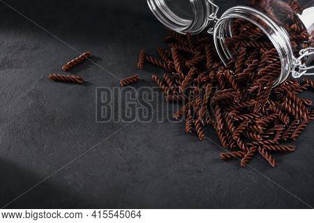 Organic Uncooked Buckwheat Fusilli Pasta In A Glass Jar On Dark Background. Wholegrain Gluten Free N