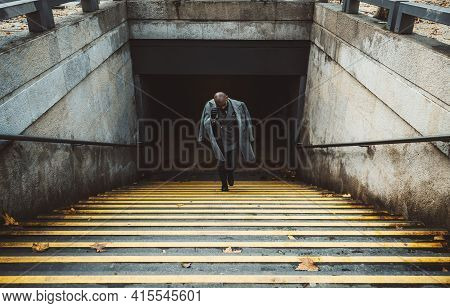 View Of An Elegant Bald Man Entrepreneur Climbing The Stairs With Yellow Lines From The Metro Statio