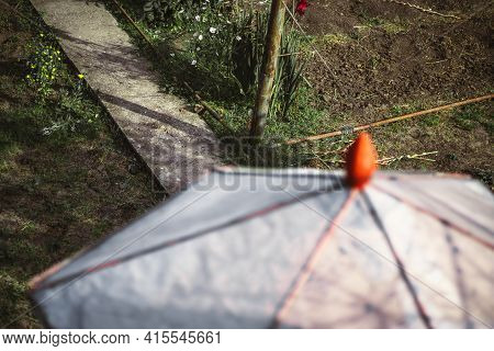 View Of A Dacha Garden With A Selective Focus On A Cement Track With Cultivated And Uncultivated Gro