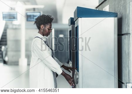 Side View Of A Fancy Young Black Female In Sunglasses And White Trench Using Indoor Atm To Withdraw