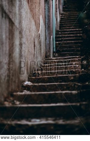 View Of A Long Dark Stone Stair Stretching Up Into The Distance Near A Wall Of An Old Building; Shal