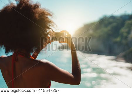 View From Behind Of A Black Svelte Female In A Swimsuit Using Her Smartphone To Take Pics Of A Tropi