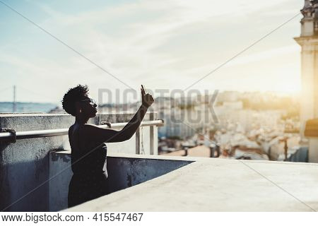 A Silhouette Of A Young Black Woman In Eyeglasses Taking Pics On Her Cellphone On The Roof With A Su
