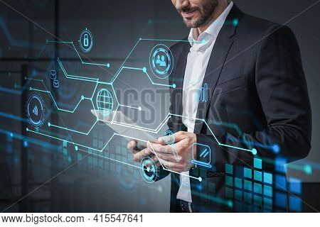 Smiling Businessman Wearing Formal Suit Is Holding Tablet And Networking With Colleagues. Office In
