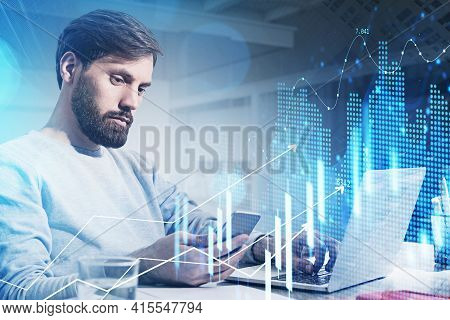 Trader With Beard Wearing White Sweater Is Sitting At Workplace Inside The Office, Holding A Smart P
