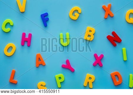The Letters Of The Alphabet Are Scattered Randomly On A Blue Background. Colorful Alphabet Letters.