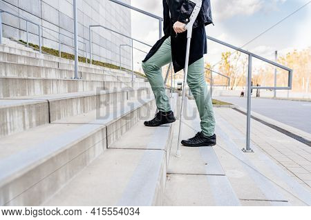 Injured Man Trying To Walk On Crutches Up The Stairs.