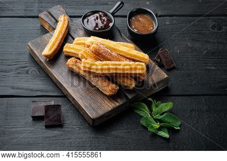 Churros With Caramel, Traditional Spanish Cusine, On Black Wooden Table Background