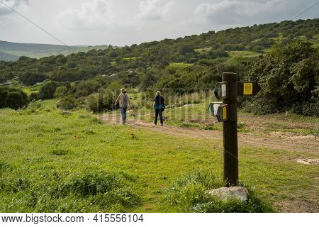 Two Hikers On A Nature Path In The Adullam Region Of Israel, Passing Near A Direction Sign, On A Haz