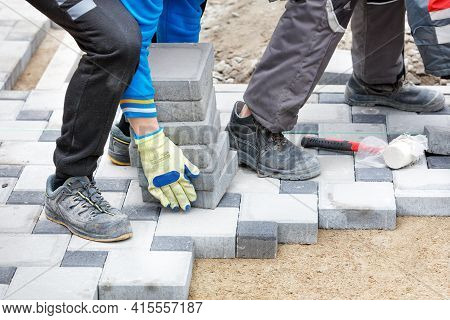 The Hands Of A Worker In Protective Gloves Raise A Stack Of Paving Slabs At The Work Site Along The