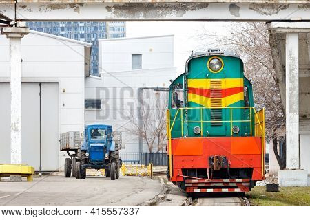 An Old Diesel Railway Locomotive In Green And Orange Colors And A Wheeled Tractor Leave The Depot Fo