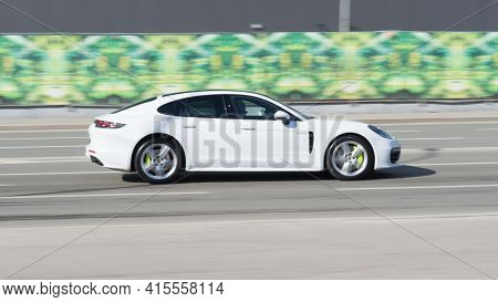 Moscow , Russia - March 2021: White Porsche Panamera On The City Road. Fast Moving Car On The Street
