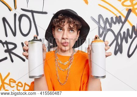 Thoughtful Hipster Guy Concentrated Above Holds Two Aerosol Bottles Wears Black Hat And Orange T Shi