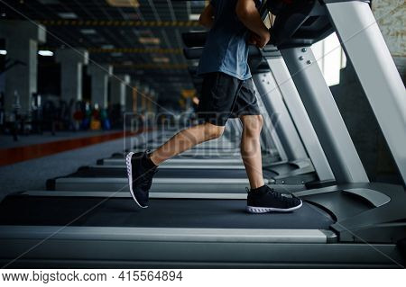 Youngster doing exercise on treadmill in gym