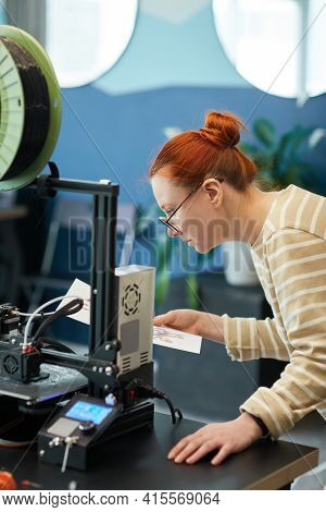 Vertical Side View Portrait Of Young Red Haired Woman Using 3d Printer In Engineering Class