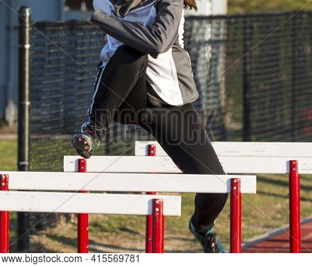 A Track And Field Hurdler Is Warming Up Performing Hurdle Drills Over Hurdles On A Track.
