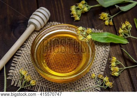 Glass Bowl With Linden Honey, Stick For Honey And Fresh Linden Flowers On A Wooden Table. Selective