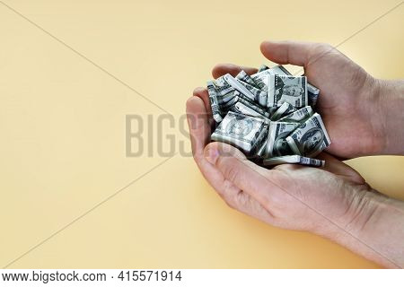 Hands Hold Handful Of Candies In Form Of Dollars. Money Depreciation And Inflation Concept, On Yello