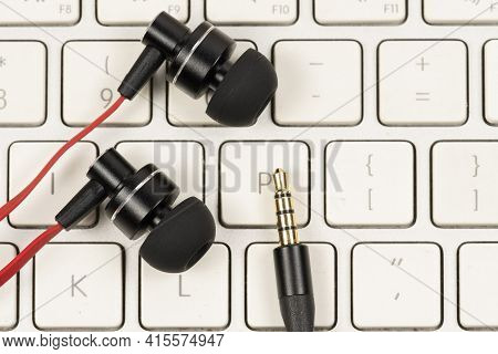 Earphone With Red Cord On Computer White Keyboard Closeup.