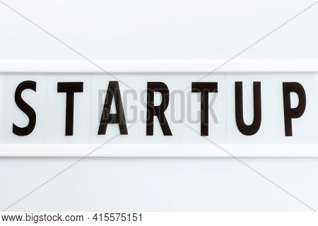 The Inscription Start-up On White Plastic Board Close-up Top View.