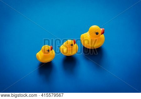 Yellow Rubber Duck Mother Leading Her Babies On Blue Background. Minimal Mother Day Concept.