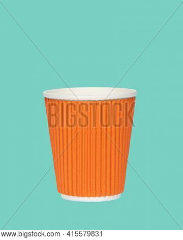 Photo of an orange paper cup on a colored green background. Photo of a coffee cup made of recyclable materials. Empty paper coffee cup.