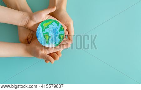Child and adult holding planet in hands on teal background. Earth day holiday concept.