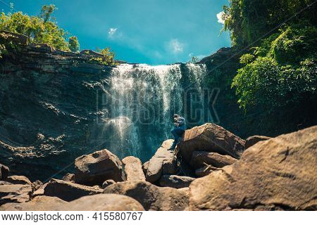 Asian Man Traveller Climbing For Overcome Stand On Stone Near Waterfall View. Waterfall In The Rainf