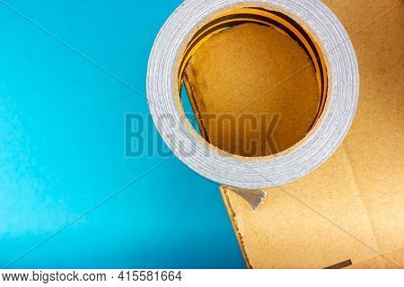 A Stream Of Duct Tape On A Cardboard Box. Parcel Packing Process. Adhesive Tape For Gluing A Cardboa